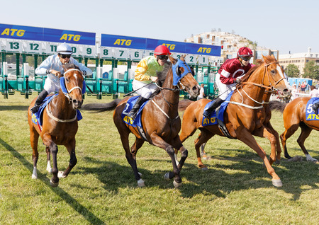 STOCKHOLM, SWEDEN - JUNE 06, 2019: Start of the gallop race for arabian race horses and colorful jockeys at ATG Nationaldags Galoppen at Gardet. June 6, 2019 in Stockholm, Sweden
