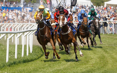 STOCKHOLM, SWEDEN - JUNE 06, 2019: Closeup of tough fight between many jockeys riding arabian race horses and audience in the background at ATG Nationaldags Galoppen at Gardet. June 6, 2019 in Stockho