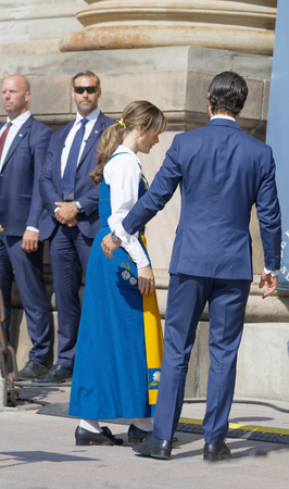 STOCKHOLM, SWEDEN - JUN 06, 2019: Rear view of the swedish prins Carl Philip Bernadotte and princess Sofia Hellqvist walking in to the royal castle. Stockholm, Sweden June 06, 2019