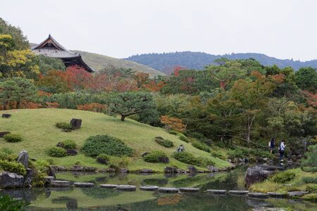 Beautiful pond and a park with red and green maple leaves during autumn in Arashiyama, Japan