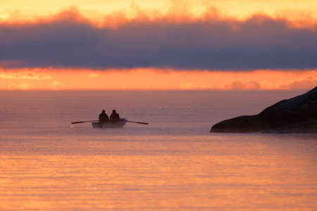 GRISSLEHAMN, SWEDEN - DEC 18, 2020Two men in a row boat during sunrise, the light is orange.Grisslehamn, Sweden December 18, 2020 Editorial