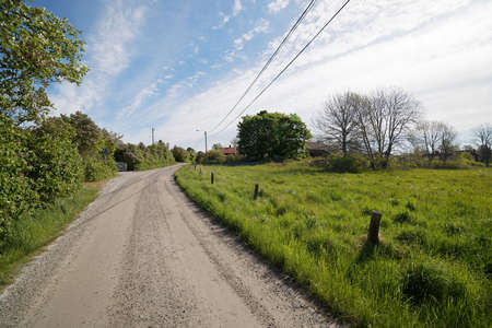 Rural country road in the small village during spring, distant red cottage and trees, blue sky