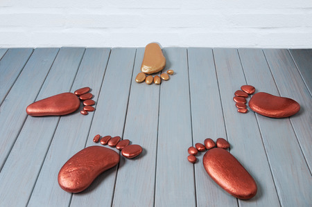 outsider: Stone foot of different color is in danger. Concept bullying or racism.