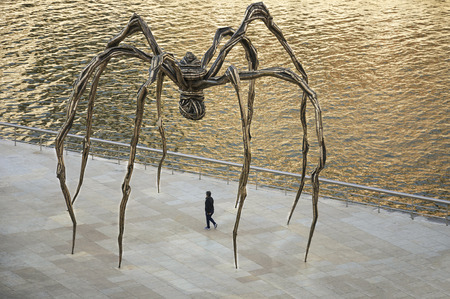 bourgeois: Woman walks under the giant spider of the artist Louise Bourgeois, outside theguggenheim museum of Bilbao, Basque Country, Spain
