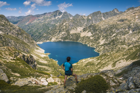 hiker contemplates from the top of the mountain, Lake Artouste, in the French Pyrenees Banco de Imagens