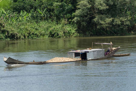 transported: gravel traditionally transported on a boat in the Mekong Delta Stock Photo