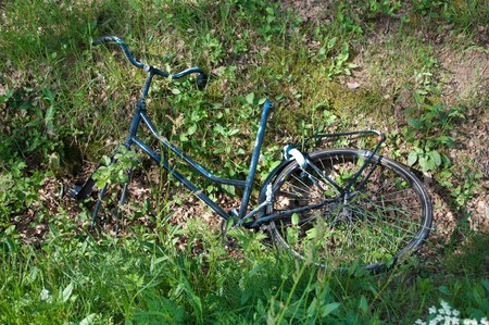 vandalism: damaged and stripped bike thrown in a ditch as a result of vandalism Stock Photo