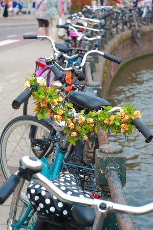 bicycle decorated with flowers besides a canal in Amsterdam Stock Photo - 7509409