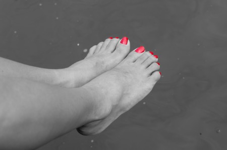 black and white pic of some tired feet above a canal after a long walk in Amsterdam. Only the nails are colored photo
