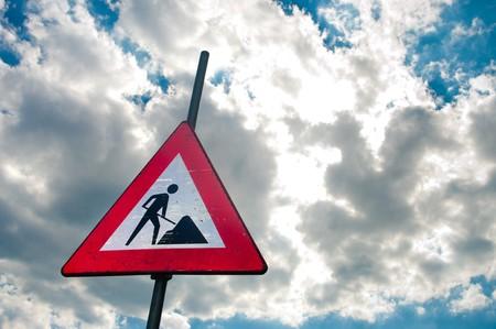 roadwork: roadwork sign against blue cloudy sky