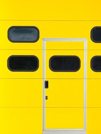 smaller: smaller door in a yellow roller door as part of a warehouse