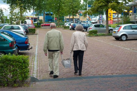 aged couple carrying together their shopping bag