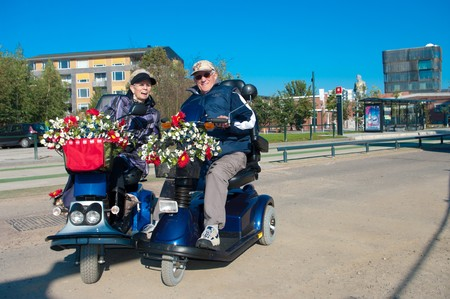 an elderly couple on their mobility scooters