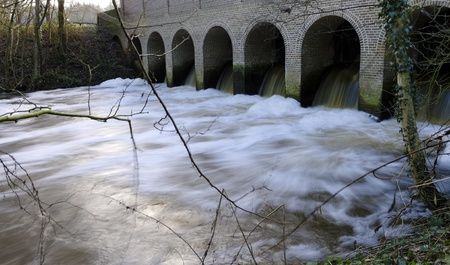 sluice: flowing water coming outside a historic sluice building Stock Photo