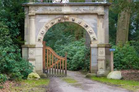 entrance arbor: ancient looking stone arch gate decorated with zodiac signs Stock Photo
