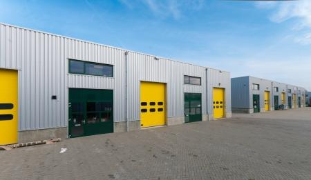 edificio industrial: nave industrial con puertas de rodillos de verde y amarillo Foto de archivo