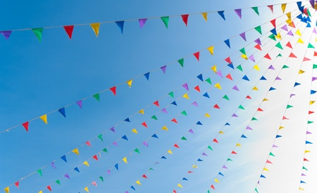 fair: bunting flags blowing in the wind against a saturated blue sky Stock Photo