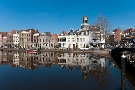 LEIDEN, NETHERLANDS - MARCH 20: monumental houses reflected in a canal on a sunny day on March 20, 2011 in Leiden, Netherlands
