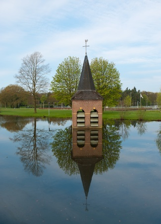 sunk: church-tower just above the water surface on the area of the technical university of enschede, netherlands. It symbolizes the dropping behind of the religious dogmas with the new scientific views.