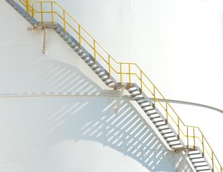 seguridad industrial: escaleras que conducen a la parte superior de un blanco gran tanque de gasolina y petr�leo en el puerto de Rotterdam
