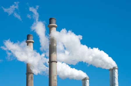 smoking chimneys from a power plant against a blue sky photo