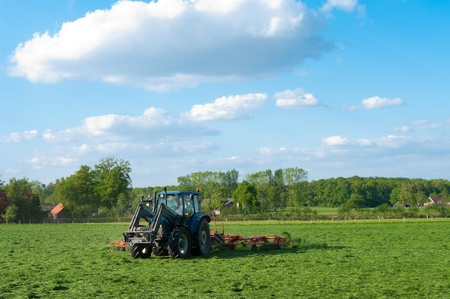 farmer busy with tractor to flip just mowed grass photo