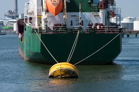 tanker moored at a yellow buoy in the rotterdam harbor photo