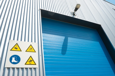 industrial park: industrial unit with blue roller door and some warning signs
