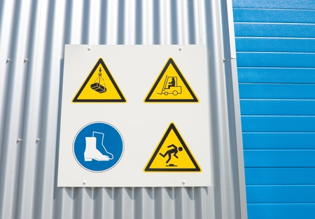health dangers: industrial warning signs on a warehouse with a blue roller door