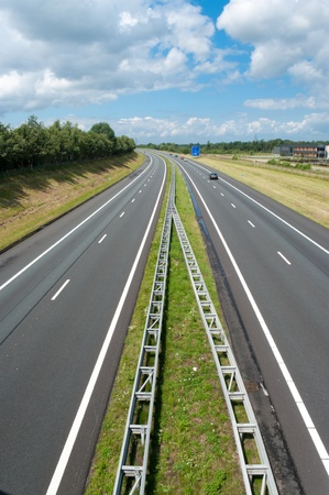 guardrail: almost empty highway in vacation time under a cloudy sky