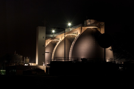 methane: sludge digestion installation on a waste water plant at night. Here is methane produced and used for the energy supply for the plant Stock Photo