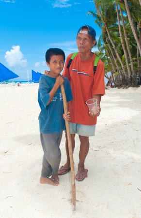 pauper: BORACAY ISLAND, PHILIPPINES - SEPTEMBER 05: Blind man with his son begging for money on September 05, 2011 on Boracay , Philippines. With no social securities this country is one of the poorest of south-east asia with over one million people living on the Editorial