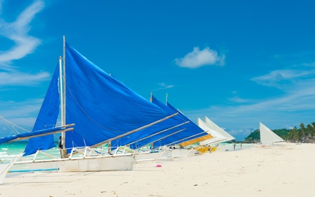traditional paraw sailing boats on white beach on boracay island, Philippines photo