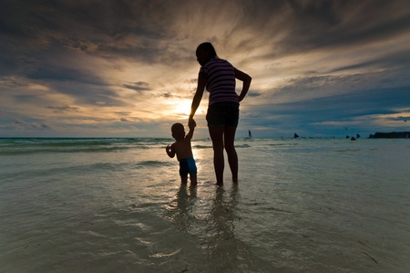 silhouette of a mother with her baby at sunset on a tropical beach photo