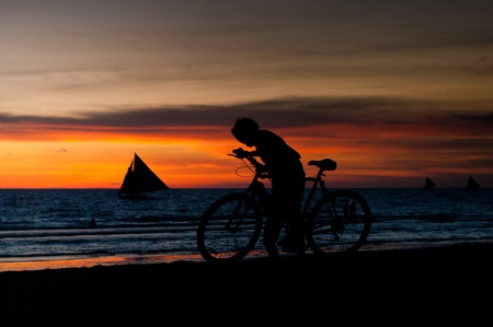 silhouette of a boy with a bicycle against a beautiful sunset photo