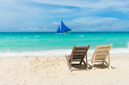 tropical beach with two beach chairs facing the blue sea photo