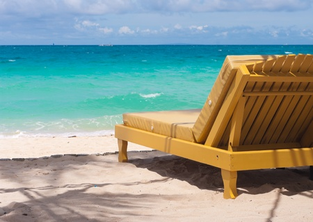tropical beach with a sunlounger facing the blue sea photo