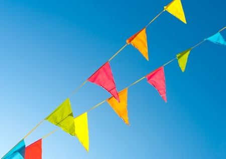 colorful bunting flags against a blue saturated sky photo