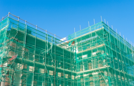 building under construction wrapped in a green net for safety Editorial