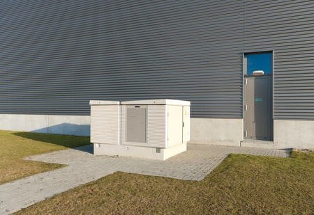transformator: small transformer house next to an industrial warehouse