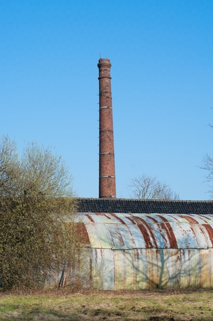 barrack: old industrial brick chimney with an old barrack