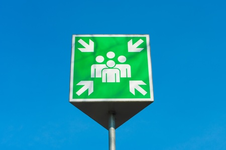 assembly point: emergency assembly point green sign against a blue sky