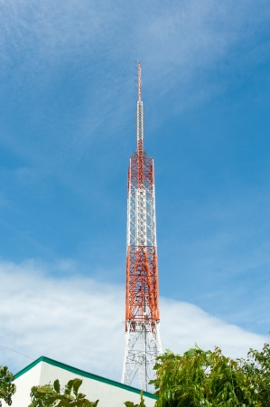 red with white radio tower against a blue sky photo