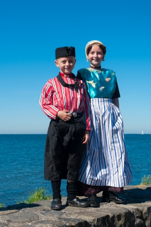 fishing fleet: Boy and girl show original costumes for tourists on the traditional Urkerdays on May 26, 2012 in Urk, Netherlands. Urk has the largest fishing fleet of the Netherlands. Editorial