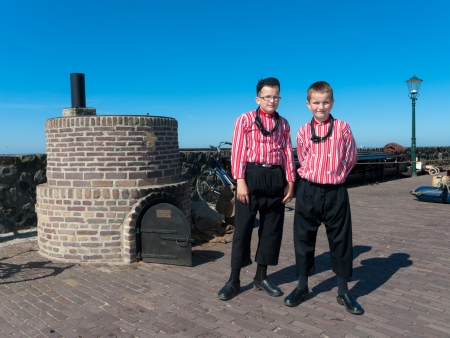 fishing fleet: Two boys show original costumes for tourists on the traditional Urkerdays on May 26, 2012 in Urk, Netherlands. Urk has the largest fishing fleet of the Netherlands.