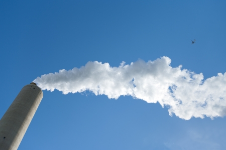 smoking industrial chimney against a blue sky with an airplane passing by Stock Photo - 14596416