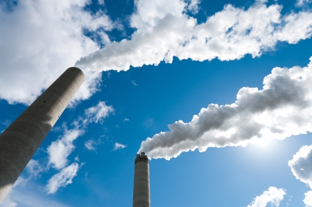 smoking industrial chimneys against a blue sky Stock Photo