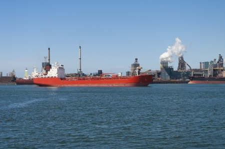 ijmuiden: red tanker passing by a large steel factory in IJmuiden, Netherlands Stock Photo