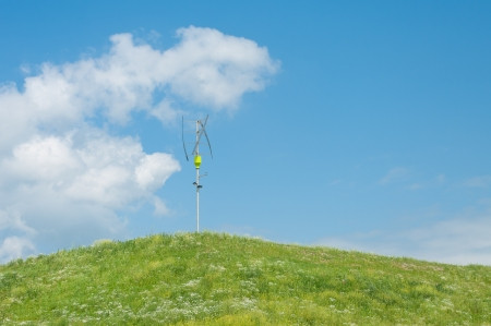 axis: small vertical axis wind turbine on a green hill