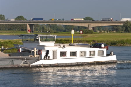 tanker barge on IJssel river in the Netherlands with a busy highway in the background photo